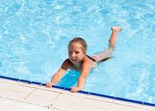 Mädchen, das am Rand des Pools sitzt Stockfotos