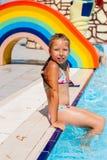Mädchen, das am Rand des Pools sitzt Lizenzfreie Stockfotos
