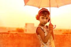 Mädchen, das Regenschirm im schönen Kleid hält Lizenzfreies Stockfoto