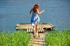 Mädchen, das in Richtung zum Fluss läuft Lizenzfreie Stockfotos