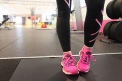 Mädchen, das rosa Laufschuhe auf Tretmühle trägt stockfotos