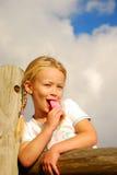 Mädchen, das rosafarbene Eiscreme isst Stockfotografie