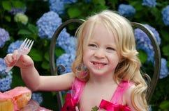 Mädchen, das rosafarbene kleine Kuchen isst Stockbilder