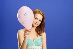 Mädchen, das rosafarbenen überraschten Ballon anhält lizenzfreies stockfoto