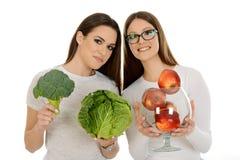 Mädchen, das rote Äpfel halten und Mädchen, das vegelables hält stockbilder
