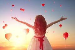 Mädchen, das rote Ballone betrachtet Stockbild