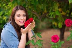 Mädchen, das rote Rosen hält Stockfoto