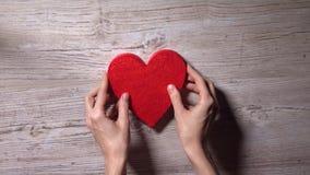 Mädchen, das rotes Herz auf einen Holztisch, Ansicht von oben setzt Einsamkeit, Liebe, Valentinstagkonzepte Video 4K stock video footage