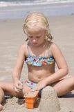 Mädchen, das Sand-Schlösser am Strand bildet Stockbilder