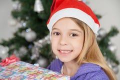 Mädchen, das Santa Hat With Christmas Gift trägt Stockbild