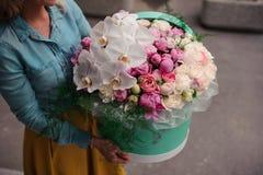 Mädchen, das schöne Mischung weißer und rosa Blumenblumenstrauß im runden Kasten mit Deckel hält Stockbild