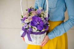 Mädchen, das schönen purpurroten Blumenstrauß von Mischblumen im Korb hält Stockfoto