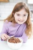 Mädchen, das Schüssel zuckerhaltige Frühstückskost aus Getreide in der Küche isst Lizenzfreies Stockbild