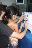 Mädchen, das Schablonespritzpistole erlernt Stockfotografie