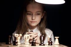 Mädchen, das Schach unter Lampe spielt Stockbild