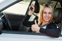 Mädchen, das Schlüssel von ihrem Neuwagen zeigt Stockfotografie