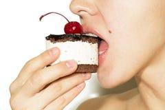 Mädchen, das Schokoladenkuchen mit Kirsche auf der Spitzenzuckerglasur isst Stockbilder