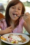 Mädchen, das Schokoladenpfannkuchen isst Lizenzfreie Stockfotos