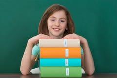 Mädchen, das am Schreibtisch mit Stapel Büchern sitzt lizenzfreies stockbild