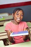 Mädchen, das Schulbuch in der Klasse hält Stockfotos