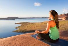 Mädchen, das am See Powell meditiert Lizenzfreie Stockfotos