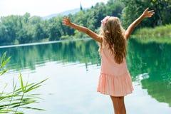 Mädchen, das am Seeufer mit den offenen Armen steht. Stockfotos