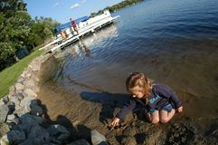 Mädchen, das Seeufer spielt Lizenzfreie Stockfotos