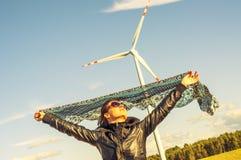 Mädchen, das Segeltuchumhang und windturbine im Hintergrund anhält Stockfotografie