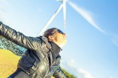 Mädchen, das Segeltuchumhang und windturbine im Hintergrund anhält Lizenzfreie Stockfotos