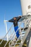 Mädchen, das Segeltuchumhang und windturbine im Hintergrund anhält Lizenzfreie Stockfotografie