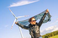 Mädchen, das Segeltuchumhang und windturbine im Hintergrund anhält Lizenzfreies Stockbild