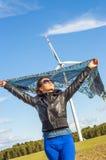 Mädchen, das Segeltuchumhang und windturbine im Hintergrund anhält Stockfotos