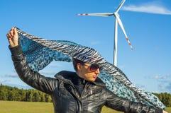 Mädchen, das Segeltuchumhang und windturbine im Hintergrund anhält Lizenzfreies Stockfoto
