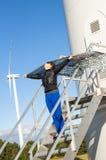 Mädchen, das Segeltuchumhang und windturbine im Hintergrund anhält Stockbild