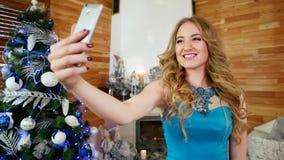 Mädchen, das selfies nimmt und Gesichter für das Foto mit Leuten, schönes festlich gekleidetes Mädchen am Weihnachtsfest zieht stock video footage