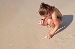 Mädchen, das Shells am Strand montiert Lizenzfreie Stockfotografie