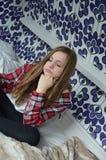 Mädchen, das sich auf einem Bett lustig und recht hinsetzt Lizenzfreies Stockfoto