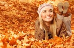 Mädchen, das sich auf herbstlichen Blättern hinlegt Stockbilder