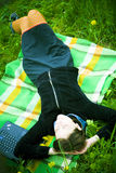Mädchen, das sich draußen auf Decke entspannt Stockbild