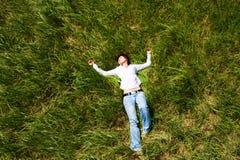 Mädchen, das sich vom Gras hinlegt Stockfotos