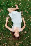 Mädchen, das sich vom Gras hinlegt Lizenzfreies Stockbild