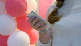 Mädchen, das Smartphone auf Hintergrund von Ballonen hält stock video footage