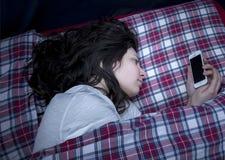 Mädchen, das Smartphone im Bett verwendet Lizenzfreie Stockbilder