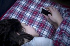Mädchen, das Smartphone im Bett verwendet Lizenzfreies Stockfoto