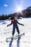 Mädchen, das Snowboard lernt lizenzfreie stockfotos