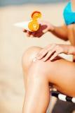Mädchen, das Sonnenschutzcreme auf Strandstuhl setzt Stockfoto