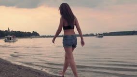Mädchen, das in Sonnenuntergang auf dem Strand durch das Wasser geht stock footage