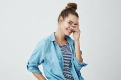 Mädchen, das späht, um Überraschung zu sehen Nettes und reizendes europäisches Mädchen mit Brötchenfrisur im Denimhemd, das Finge lizenzfreie stockbilder