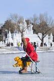 Mädchen, das Spaß mit dem Sledging auf Eis in Nanhu-Park, Changchun, China hat Stockfotografie