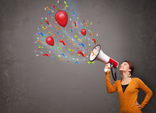 Mädchen, das Spaß, schreiend in Megaphon mit Ballonen und Konfettis hat Stockbild